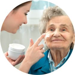 nurse applying skin care on an elderly