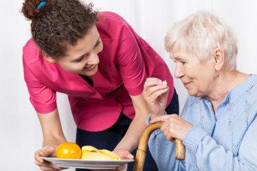 nurse handing a tray of food